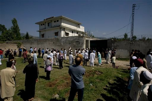 Local people and media gather outside the perimeter wall and sealed gate into the compound and a house where al-Qaida leader Osama bin Laden was caught and killed late Monday, in Abbottabad, Pakistan, on Tuesday, May 3, 2011.