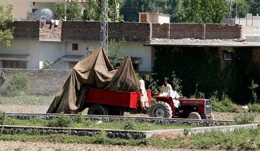FILE - In this May 2, 2011 file photo, a tractor trolley carries the wreckage of a helicopter that crashed next to the wall of a compound where according to officials, Osama bin Laden was shot and killed in a firefight with U.S. forces in Abbottabad, Paki
