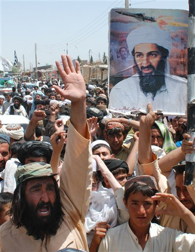 Supporters of Pakistani religious party Jamiat Ulema-e-Islam burn chants anti-U. S. slogans at rally to condemn the killing of al-Qaida leader Osama bin Laden, seen in portrait at top right, in Kuchlak, Pakistan.