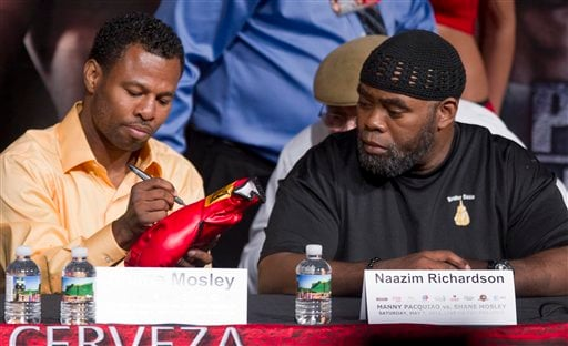 Shane Mosley, left, signs a glove for a fan as his trainer, Naazim Richardson, looks on before a news conference Wednesday, May 4, 2011, in Las Vegas.