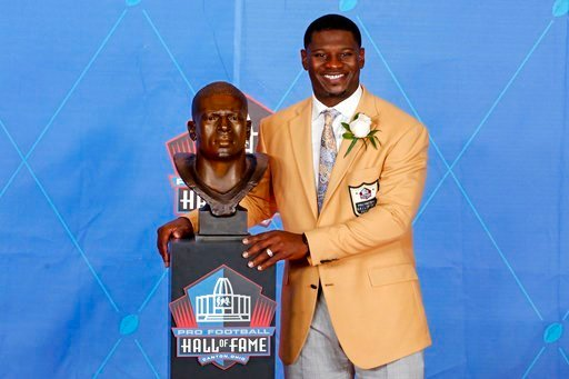Former NFL player LaDainian Tomlinson poses with a bust of himself during an induction ceremony at the Pro Football Hall of Fame, Saturday, Aug. 5, 2017, in Canton, Ohio.