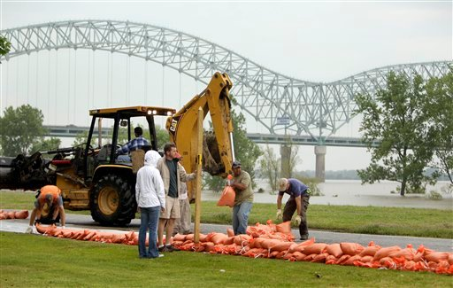 Workers construct a temporary sandbag wall around apartments and condominiums on Mud Island as the Mississippi River rises in the background Saturday, May 7, 2011, in Memphis, Tenn. (AP Photo/Jeff Roberson)