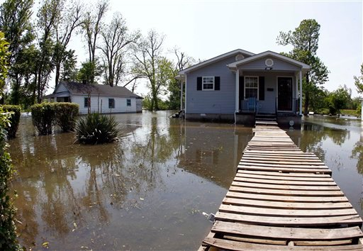 Wooden shipping pallets make a walkway to a home as it sits flooded Saturday, May 7, 2011 in Tiptonville, Tenn. (AP Photo/Wade Payne)