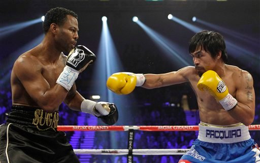 Shane Mosley, left, and Manny Pacquiao exchange punches in the second round during a WBO welterweight title bout, Saturday, May 7, 2011, in Las Vegas.
