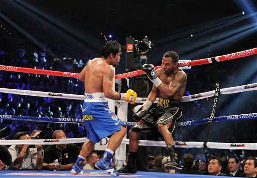 Manny Pacquiao, left, attacks Shane Mosley against the ropes in the 11th round.