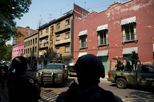 Police guard a gate to the attorney general's office for organized crime as trucks of soldiers arrive, soon after a convoy entered carrying Damaso Lopez in Mexico City, Tuesday, May 2, 2017. (AP Photo/Rebecca Blackwell)