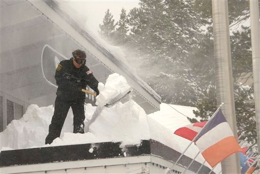 Brandon Hurt shovels snow from the roof of a shop at Squaw Valley Tuesday, Nov. 23, 2010. The Tahoe ski resort has received more than 100 inches of snow since the storm began. (AP Photo/Reno Gazette-Journal, Tim Dunn)
