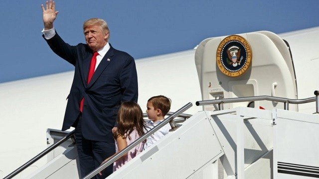 President Donald Trump waves as he walks down the steps of Air Force One with his grandchildren, Arabella Kushner, center, and Joseph Kushner, right.