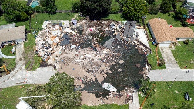 Photo shows a large sinkhole in the Lake Padgett Estates community in Land O' Lakes, Fla.