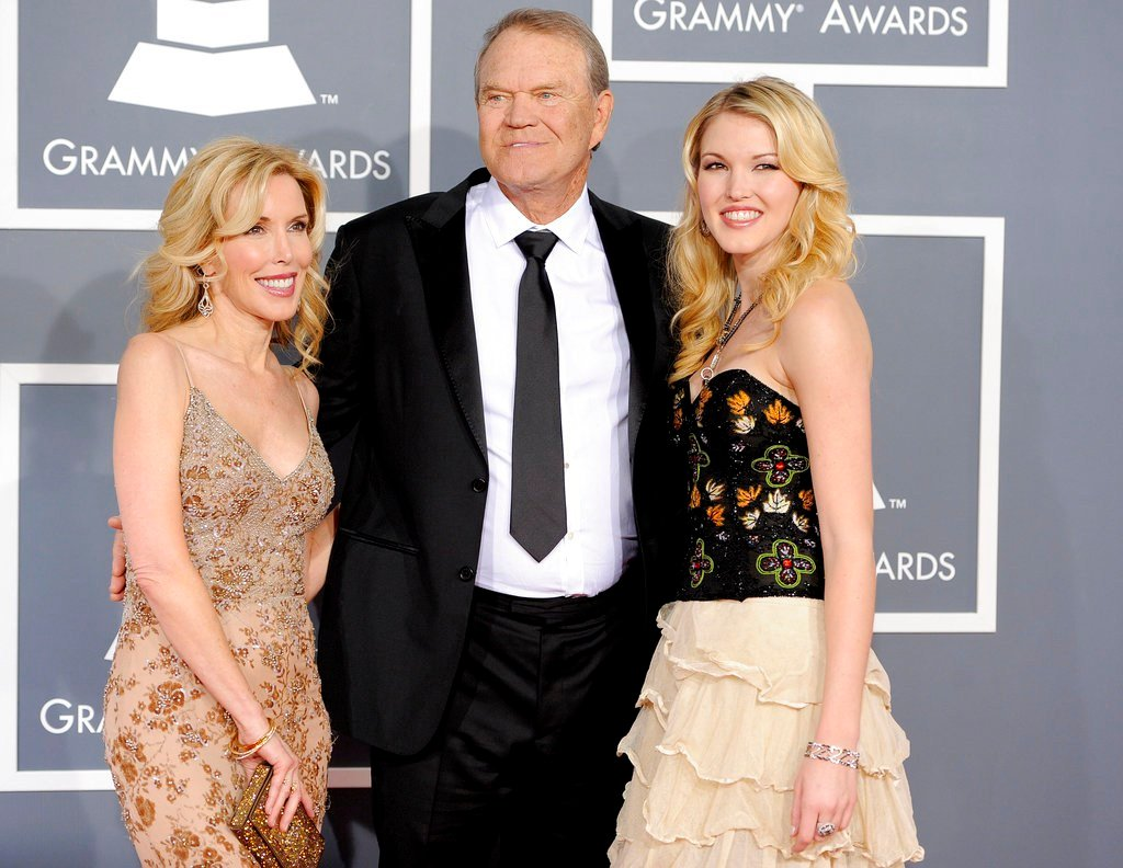 In this Feb. 12, 2012 file photo, Glen Campbell, center, Kim Woolen, left, and Ashley Campbell arrive at the 54th annual Grammy Awards in Los Angeles. (AP Photo/Chris Pizzello, File)