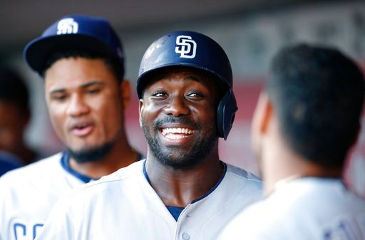 San Diego Padres left fielder Jose Pirela, center wears a big smile after a two-run homer off Cincinnati Reds starting pitcher Sal Romano (47) during the first inning of a baseball game, Tuesday, Aug. 8, 2017, in Cincinnati. (AP Photo/Gary Landers)