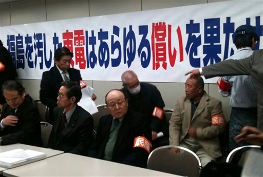 Angry residents forced from their homes near Japan's tsunami-stricken Fukushima Dai-ichi nuclear power plant take seat as they meet officials of Tokyo Electric Power Co., the plant's operator, at its headquarters in Tokyo Wednesday, April 13, 2011.