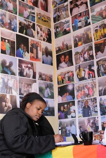 In this photo taken Friday, May 6, 2011, gay rights activist, Bontle Khalo, sits beneath sociable photos of the local gay community in the offices of the local organising committee offices in Kwa Thema, east of Johannesburg.