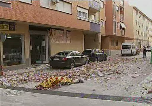 A body lies covered on the ground near damaged vehicles on a street after an earthquake in Lorca Spain in this image taken from TV Wednesday May 11, 2011.