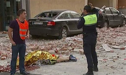 Emergency personnel attend the scene as a body lies covered on the ground after an earthquake in Lorca Spain in this image taken from TV.