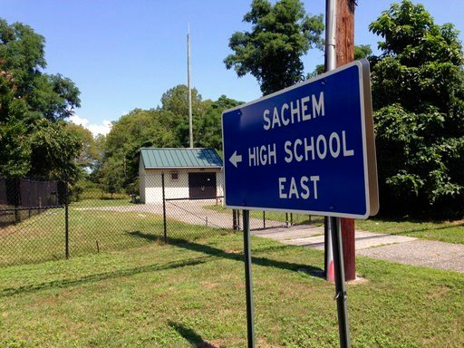 A sign points to Sachem East High School in Farmingville, N.Y. where police say log fell on a teenage football player's head, killing him, Thursday Aug. 10, 2017.