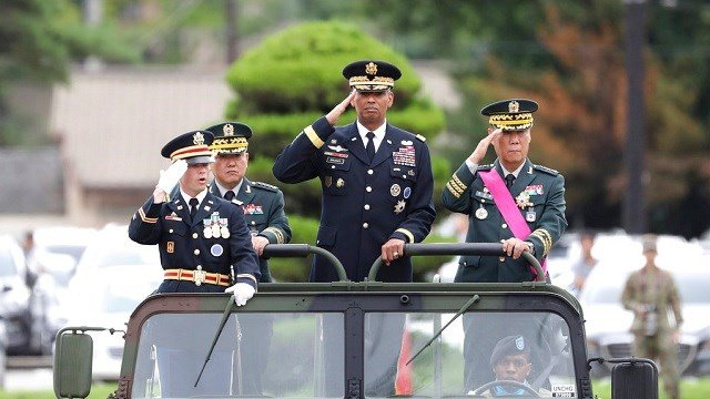 U.S. Gen. Vincent Brooks, commander of Combined Forces Command, center, salutes with incoming Deputy Commander Gen. Kim Byung-joo, left rear, and outgoing Deputy Commander Gen. Leem Ho-young, right, in a car.
