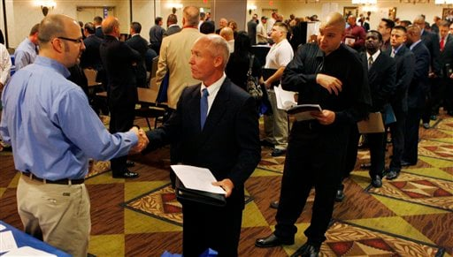 In this May 3, 2011 photo, as a long line of job-seekers wait, Lockheed Martin military relations manager Dave Wallace, left, shakes hands with Joe Archatowski, of Lansdale, Pa.,at a job fair.