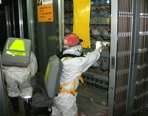 In this May 10, 2011 photo released by Tokyo Electric Power Co., a worker checks the status of the water level indicator at the Unit 1 reactor building at the Fukushima Dai-ichi nuclear power plant in Okuma town, Fukushima prefecture, northern Japan.