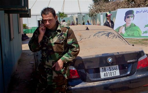 In this photo taken on a government organized tour, a Libyan soldier uses his cellphone at the site of an airstrike, at Bab al-Azaziya compound in Tripoli, Libya, Thursday, May 12, 2011.