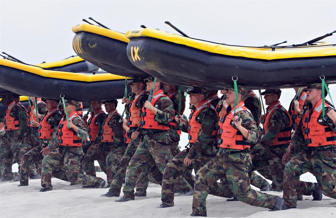 FILE - In this May 14, 2009 file photo, Navy SEAL trainees carry inflatable boats at the Naval Amphibious Base Coronado in Coronado, Calif.(AP Photo/Denis Poroy, File)