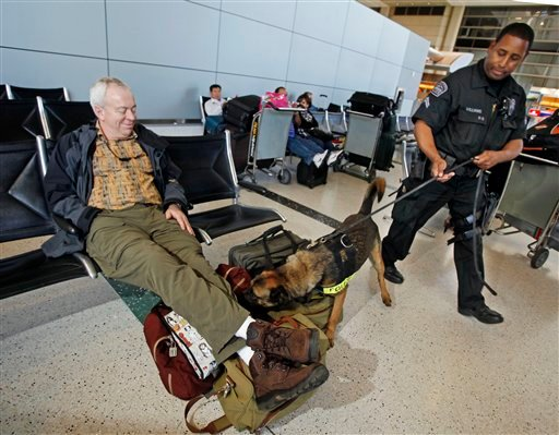 "Airport police officer Eric Williams and ""Buc,"" a 3-year-old Belgian Malinois, check waiting passengers after a news conference and demonstration of dogs that are trained to sniff for explosives, primarily on the bodies of people as well as in luggage."