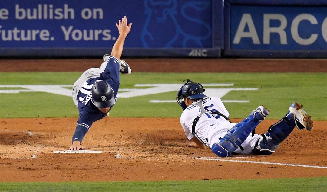 San Diego Padres' Hunter Renfroe, left, reaches for the base after being tagged out by Los Angeles Dodgers catcher Austin Barnes while trying to score on a single by Cory Spangenberg during the third inning of a baseball game, Friday, Aug. 11, 2017, in Lo