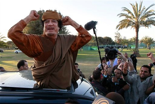 FILE - In this April 10, 2011 file photo, Libyan leader Moammar Gadhafi waves at his supporters people in Tripoli, Libya. Moammar Gadhafi says he's alive after NATO attacks and has support of millions of Libyans.