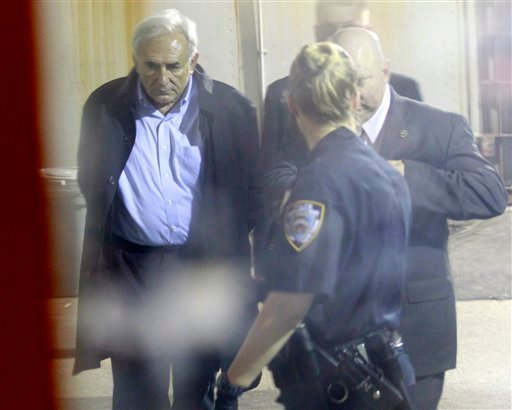 International Monetary Fund leader Dominique Strauss-Kahn, left, is seen through a window as he is checked into Municipal Court, Monday, May 16, 2011 in New York. Strauss-Kahn is accused of sexually assaulting a maid in his hotel room in New York City.