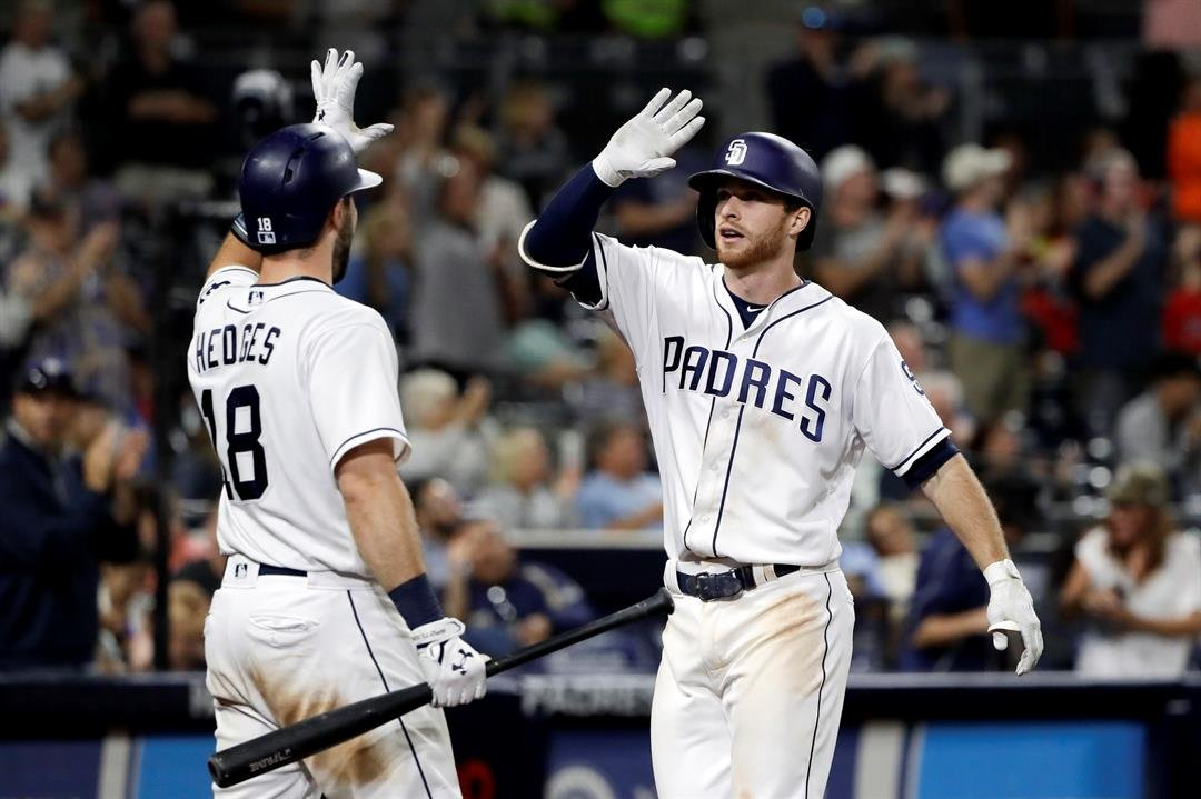 San Diego Padres' Cory Spangenberg, right, greets teammate Austin Hedges (18) after hitting a home run during the seventh inning of a baseball game against the Philadelphia Phillies Monday, Aug. 14, 2017, in San Diego. (AP Photo/Gregory Bull)