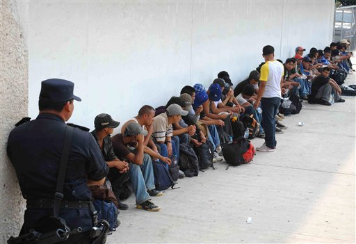 Migrants who were found in two trailer trucks bound for the United States, sit under the guard of a policeman in Tuxtla Gutierrez, Mexico, Tuesday May 17, 2011.