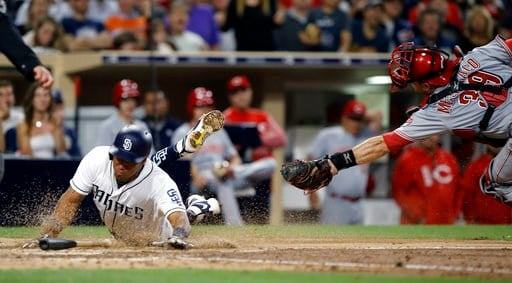 San Diego Padres' Yangervis Solarte dives for home, scoring from third after teammate Cory Spangenberg steals second base during the fifth inning of a baseball game Tuesday, Aug. 15, 2017, in San Diego. Philadelphia Phillies catcher Jorge Alfaro grabs the