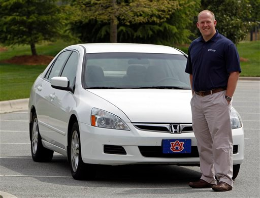 In this April 20, 2011 photo, Jeremy Barnes poses in front of the 2007 Honda he is selling near his home in Greensboro, N.C. (AP Photo/Chuck Burton)