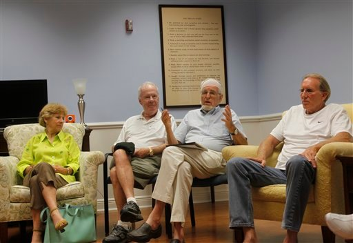 In this April 7, 2011 photo, 83-year-old Gifford Dean, second from right, his head wrapped in gauze from a recent surgery, leads participants in a support group for older adults at the Hanley Center. (AP Photo/Wilfredo Lee)