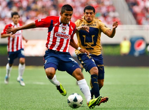 Pumas' Martin Bravo, right, and Chivas' Miguel Ponce, left, fight for the ball during a Mexican soccer league match in Guadalajara, Mexico, Thursday May 12, 2011.
