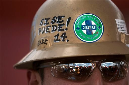 """Shipyard worker Julian Cruz, of San Diego, wears a helmet with the words, """"yes, it can be done,"""" a motto of the United Farm Workers union, during a naming ceremony for a new Navy ship at a shipyard Wednesday, May 18, 2011, in San Diego."""