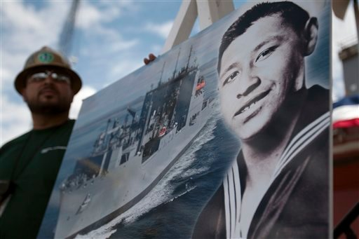 Shipyard worker Julian Cruz, left, holds a picture showing the late farm labor leader Cesar Chavez during his stint in the Navy, alongside an image of a T-AKE class dry cargo and ammunition ship during a naming ceremony.