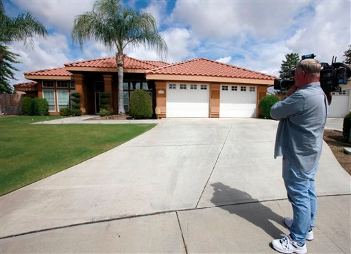 Stephen Coleman, a cameraman for ABC News, photographs the home believed to be the residence of a household staff member who mothered a child with former Gov. Arnold Schwarzenegger, Wednesday, May 18, 2011, in Bakersfield, Calif..
