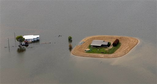 A farmhouse is protected by a small levee while another stands flooded near Yazoo City, Miss., Thursday, May 19, 2011.