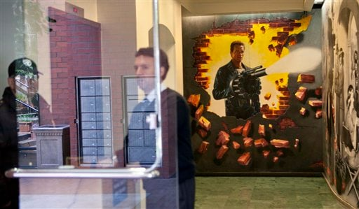 Security guards are shown in the lobby of the office building of former California Governor Arnold Schwarzenegger decorated with a movie themed mural Wednesday, May 18, 2011, in Santa Monica, Calif.