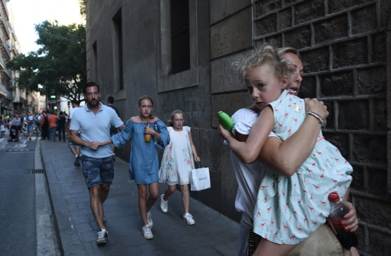 People flee the scene in Barcelona, Spain, Thursday, Aug. 17, 2017 after a white van jumped the sidewalk in the historic Las Ramblas district, crashing into a summer crowd of residents and tourists and injuring several people, police said.