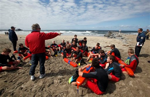 In this May 15, 2011 photo, John Carpenter, center, seasonal lifeguard cadet coordinator, instructs trainees with lifeguard captain Mike Halphide, left rear, and officer Gary Conwell, right.