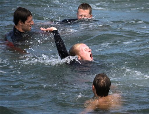 In this May 15, 2011 photo, a trainee plays the role of a swimmer in distress as other trainees come to his rescue during a training session for new seasonal lifeguards at Newport Beach, Calif.