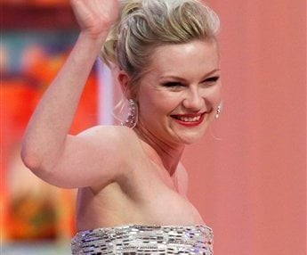 Actress Kirsten Dunst gestures to the crowd as she goes to accept the Best Actress award for the film Melancholia during the awards ceremony. (AP Photo/Francois Mori)