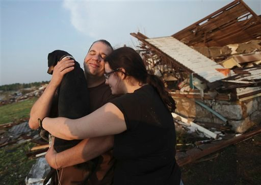 Maggie Kelley and her husband, Trey Adams hug their dog, Saint, after finding him amid the rubble of her home in Joplin, Mo. Monday, May 23, 2011.