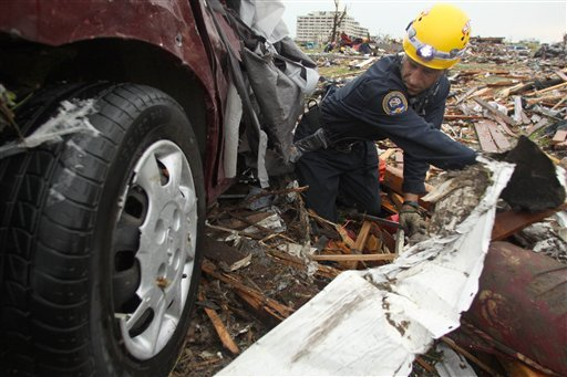 Rescue specialist Kris Tate of the Springfield, Mo., Fire Department digs under a destroyed vehicle at a home near the St. John's Regional Medical Center in Joplin, Mo., Monday, May 23, 2011.