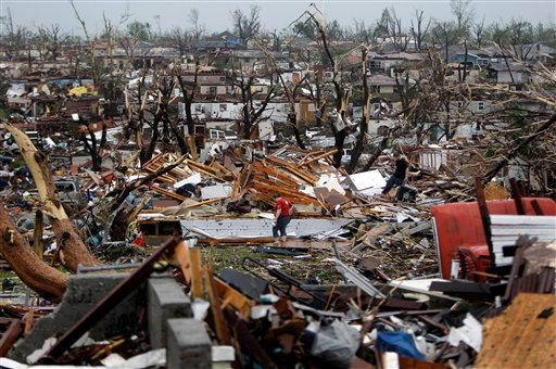 Meghan Miller stands in the middle of a destroyed neighborhood as she checks on her sister-in-law's home Monday, May 23, 2011, in Joplin , Mo.