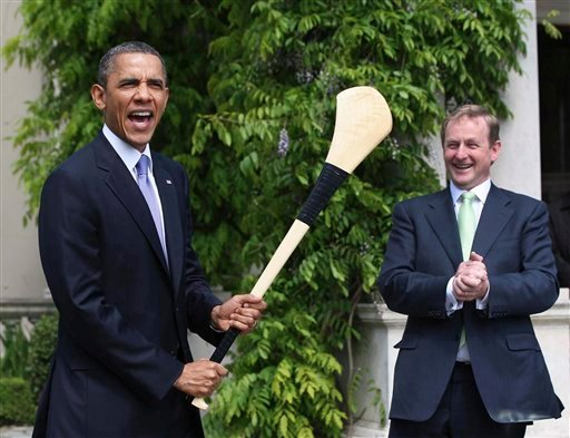 US President Barack Obama, left, reacts after he was presented with a hurley stick from Irish Prime Minister and Taoiseach Enda Kenny while in Farmleigh, Dublin Monday May 23, 2011.