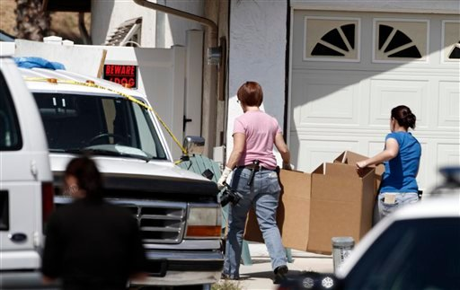 Officials walk towards the house where four people were found dead carrying empty boxes Tuesday, May 24, 2011.