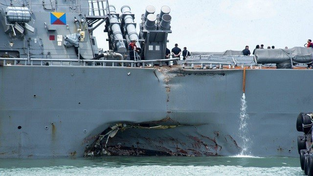 Damage to the portside is visible as the Guided-missile destroyer USS John S. McCain (DDG 56) steers towards Changi naval base in Singapore.